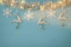 Fondo de la Navidad con la guirnalda festiva del árbol, los ciervos blancos, y los copos de nieve blancos de papel sobre fondo az Foto de archivo libre de regalías