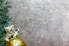 Fondo de la Navidad con la bola de oro y nieve en el tablero de madera Fotos de archivo libres de regalías