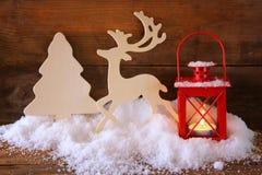 Fondo de la Navidad con la linterna roja, el reno decorativo de madera y el árbol en la nieve sobre fondo de madera Imagen de archivo