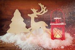 Fondo de la Navidad con la linterna roja, el reno decorativo de madera y el árbol en la nieve sobre fondo de madera Foto de archivo libre de regalías