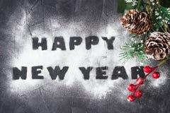 Fondo de la Navidad con la rama del árbol de navidad y de la Feliz Año Nuevo de las palabras hechos del azúcar en polvo Idea crea Fotografía de archivo libre de regalías