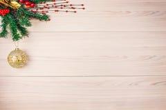 Fondo de la Navidad con la rama del abeto y bola del oro en la tabla Fotografía de archivo libre de regalías