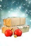 Fondo de la Navidad con las bolas de la Navidad y las cajas de regalo rojas en nieve en fondo de la noche del brillo Imagen de archivo