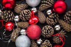 Fondo de la Navidad con las bolas y pinecone de plata rojos Foto de archivo