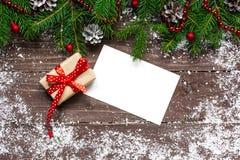 Fondo de la Navidad con las decoraciones y caja de regalo con la tarjeta de felicitación Imagen de archivo libre de regalías