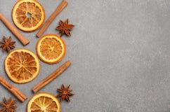 Fondo de la Navidad con las especias del invierno y las rebanadas de naranja secada Fotografía de archivo libre de regalías
