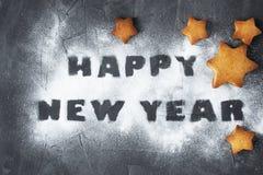 Fondo de la Navidad con las estrellas cocidas del pan de jengibre y la Feliz Año Nuevo de las palabras hechas del azúcar en polvo Imagenes de archivo