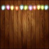 Fondo de la Navidad con las luces de la Navidad de madera Foto de archivo