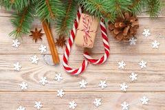 Fondo de la Navidad con las ramas de árbol de navidad, los conos del pino, los dulces del bastón de caramelo, los regalos, el cop Imágenes de archivo libres de regalías