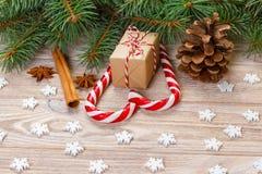 Fondo de la Navidad con las ramas de árbol de navidad, los conos del pino, los dulces del bastón de caramelo, los regalos, el cop Fotografía de archivo