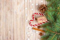 Fondo de la Navidad con las ramas de árbol de navidad, los conos del pino, los dulces del bastón de caramelo, los regalos, el cop Fotografía de archivo libre de regalías