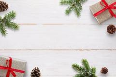 Fondo de la Navidad con las ramas del abeto, de los pinecones y de las cajas de regalo en el tablero de madera blanco Imagen de archivo libre de regalías