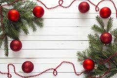 Fondo de la Navidad con las ramas del abeto y las decoraciones rojas en wh Imagenes de archivo