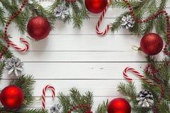 Fondo de la Navidad con las ramas del abeto y las decoraciones rojas en wh Fotos de archivo