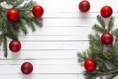 Fondo de la Navidad con las ramas del abeto y las decoraciones rojas en wh Fotografía de archivo libre de regalías