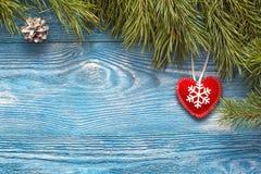Fondo de la Navidad con las ramas del abeto y el corazón del invierno en azul Fotografía de archivo