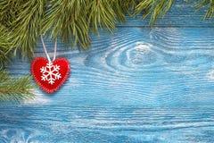 Fondo de la Navidad con las ramas del abeto y el corazón del invierno en azul Fotos de archivo