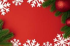 Fondo de la Navidad con las ramas rojas de la bola y del abeto, copo de nieve en fondo de papel rojo Decoración del invierno fotografía de archivo