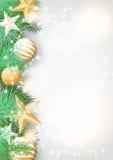 Fondo de la Navidad con las ramas verdes y los ornamentos amarillos Foto de archivo