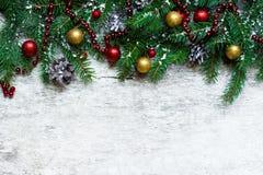 Fondo de la Navidad con las ramas y las decoraciones del abeto cubiertas con nieve Imagen de archivo libre de regalías