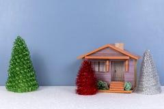 Fondo de la Navidad con los árboles de la pequeña casa y de los juguetes Imagen de archivo libre de regalías