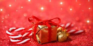 Fondo de la Navidad con los bastones de caramelo, el regalo y el brillo Imagen de archivo libre de regalías
