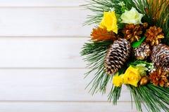 Fondo de la Navidad con los conos de oro del pino y el ro amarillo de la tela Fotografía de archivo