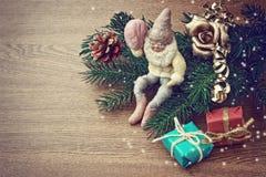 Fondo de la Navidad con los conos del pino, el regalo y el viejo gnomo Fotos de archivo