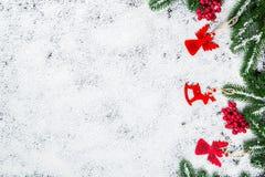 Fondo de la Navidad con los copos de nieve, la nieve blanca, los juguetes, el caramelo, las ramas de árbol de navidad y la decora Foto de archivo libre de regalías