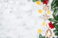 Fondo de la Navidad con los copos de nieve, la nieve blanca, los juguetes, el limón, el caramelo, las ramas de árbol de navidad y Foto de archivo libre de regalías