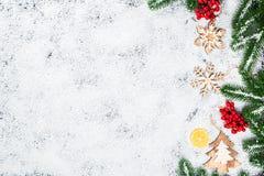 Fondo de la Navidad con los copos de nieve, la nieve blanca, los juguetes, el limón, el caramelo, las ramas de árbol de navidad y Imagen de archivo libre de regalías