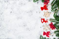 Fondo de la Navidad con los copos de nieve, la nieve blanca, los juguetes, el limón, el caramelo, las ramas de árbol de navidad y Fotos de archivo