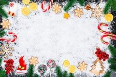 Fondo de la Navidad con los copos de nieve del pan de jengibre, la nieve blanca, los juguetes, el limón, el caramelo, las ramas d Fotos de archivo