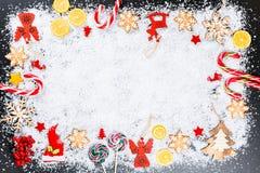 Fondo de la Navidad con los copos de nieve del pan de jengibre, la nieve blanca, los juguetes, el limón, el caramelo, las ramas d Imágenes de archivo libres de regalías