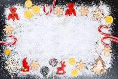 Fondo de la Navidad con los copos de nieve del pan de jengibre, la nieve blanca, los juguetes, el limón, el caramelo y la decorac Fotos de archivo libres de regalías