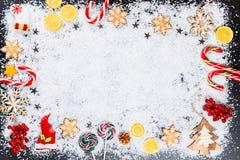 Fondo de la Navidad con los copos de nieve del pan de jengibre, la nieve blanca, los juguetes, el limón, el caramelo y la decorac Imagen de archivo libre de regalías