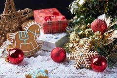 Fondo de la Navidad con nieve, la decoración roja del invierno y las galletas del copo de nieve Foto de archivo libre de regalías