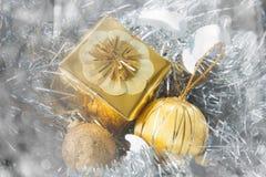 Fondo de la Navidad con un ornamento del oro y una caja de regalo de oro Imagenes de archivo