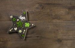 Fondo de la Navidad con una estrella hecha a mano del deco de madera y verde Foto de archivo libre de regalías