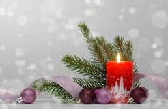 Fondo de la Navidad con la vela roja y las chucherías púrpuras Fotografía de archivo libre de regalías