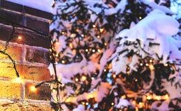 Fondo de la Navidad de la pared de ladrillo con brillar intensamente y nieve de las luces Fotos de archivo