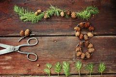 Fondo de la Navidad en los viejos tableros de madera con el elemento decorativo en la forma de un cuadro ocho, de las tijeras ant Foto de archivo libre de regalías