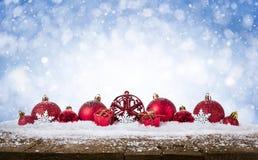 Fondo de la Navidad - las bolas rojas adornadas en nieve con el snowflakesand protagonizan en el escritorio de madera fotos de archivo