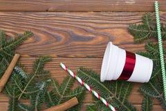 Fondo de la Navidad de madera o del Año Nuevo con las ramas de árbol de abeto, la taza de papel y el canela Imagen de archivo