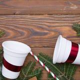Fondo de la Navidad de madera o del Año Nuevo con las ramas de árbol de abeto y las tazas de papel Imagen de archivo