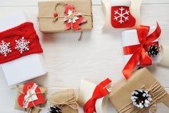 Fondo de la Navidad de la maqueta - caja de regalos del regalo de Navidad y elementos rojos del adornamiento en el fondo de mader Foto de archivo
