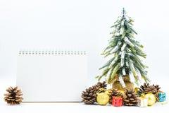 Fondo de la Navidad o del Año Nuevo con el cuaderno de notas en blanco, conos del pino, Imagenes de archivo