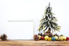 Fondo de la Navidad o del Año Nuevo con el cuaderno de notas en blanco, conos del pino, Imagen de archivo