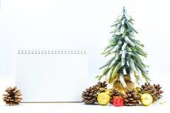 Fondo de la Navidad o del Año Nuevo con el cuaderno de notas en blanco, conos del pino, Fotografía de archivo libre de regalías