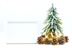 Fondo de la Navidad o del Año Nuevo con el cuaderno de notas en blanco, conos del pino, Imágenes de archivo libres de regalías